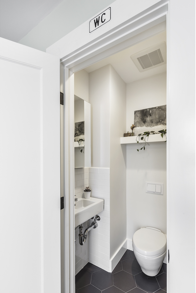 powder room with white and grey tile and floor mouted toilet and wall mounted sink.png