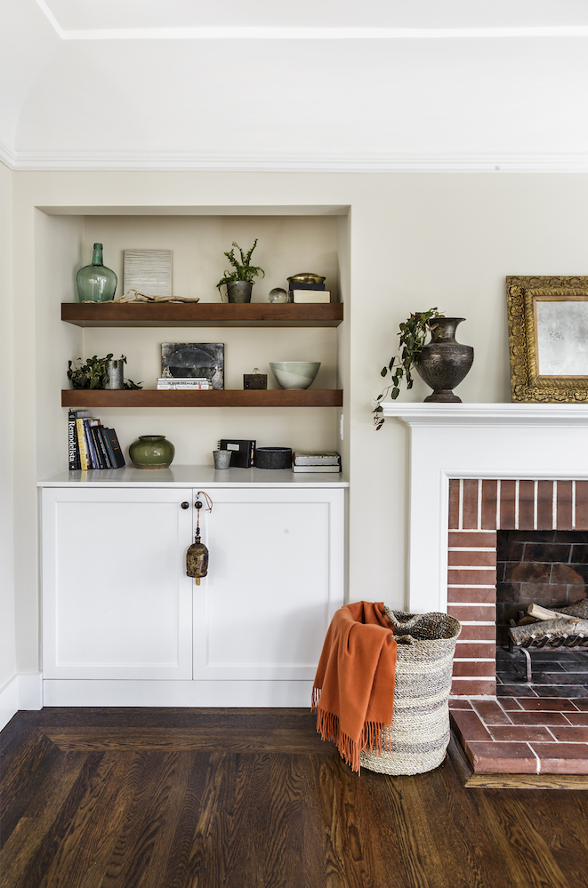 wood shelving with white storage cabin and brick fireplace with white mantel and wood flooring.png