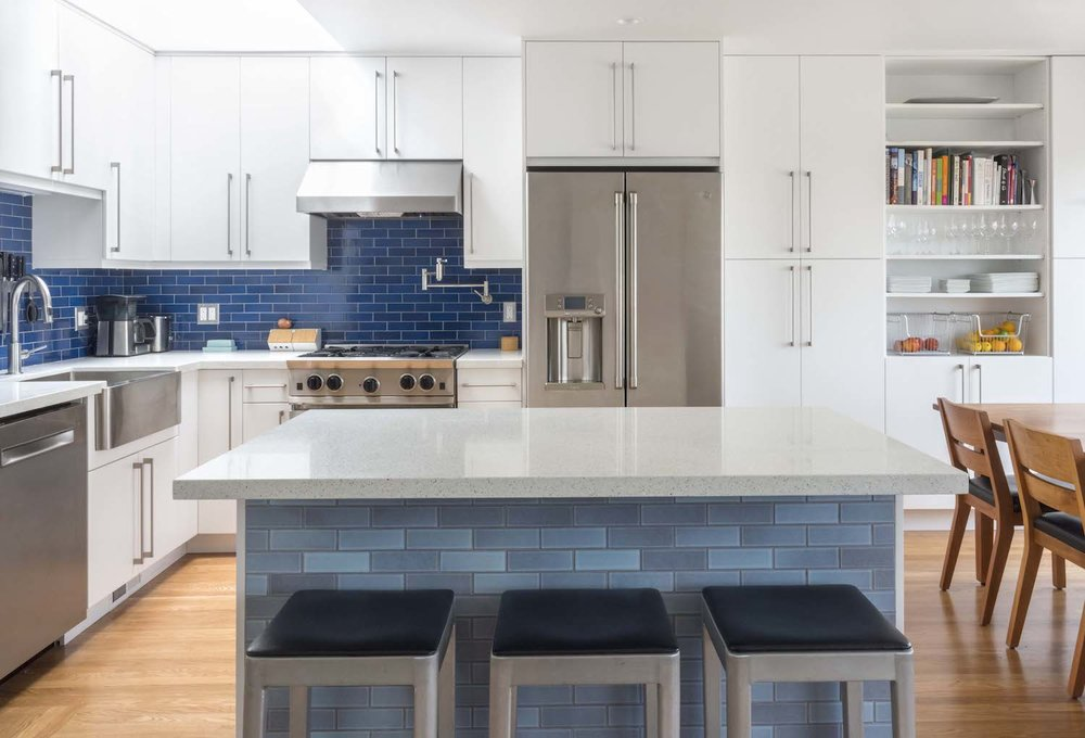 kitchen with white cabinets and open shelving and blue backsplash tile and stainless steel appliances.jpg