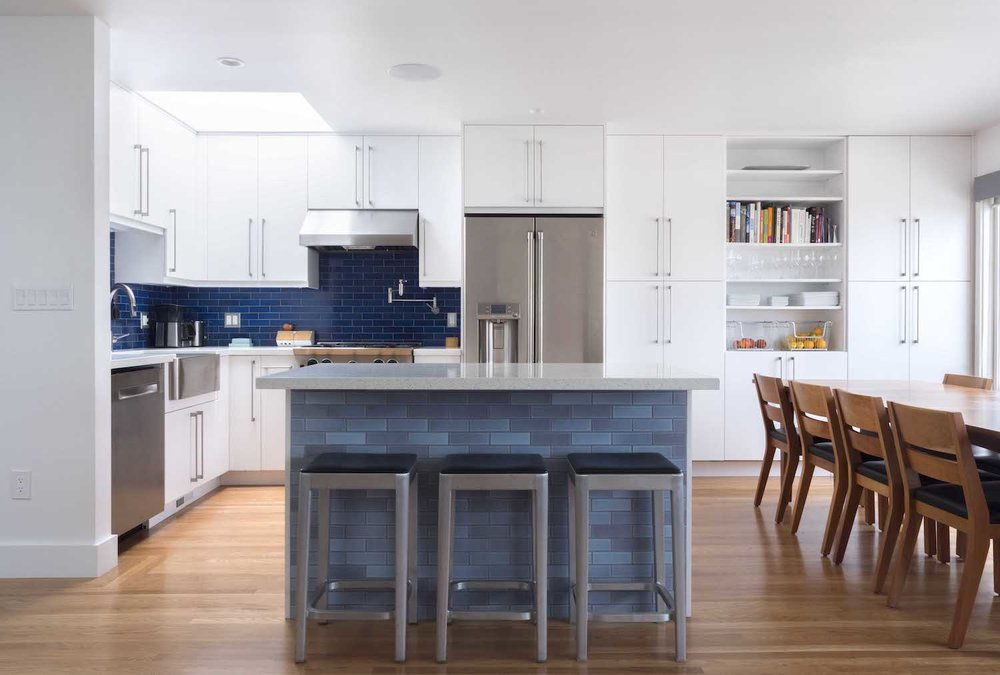 kitchen with white cabinets and open shelving and blue tile backsplash and wood flooring and stainless steel appliances.jpg