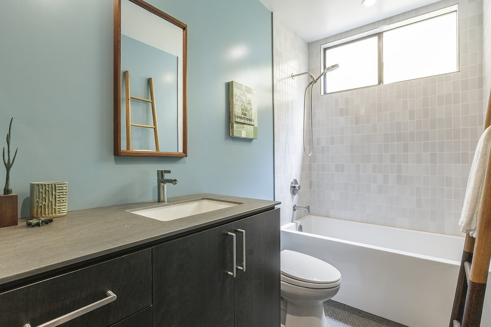 bathroom with blue painted walls and dark wood vanity and combination tub shower with grey wall tile and chrome fixtures.jpg