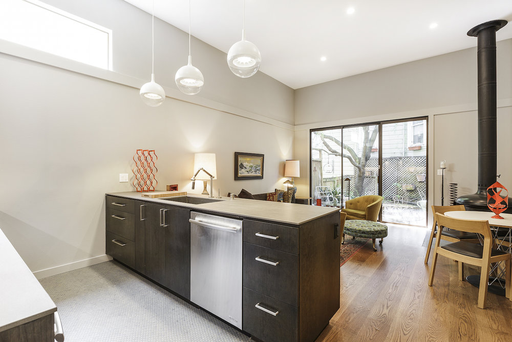 kitchen and living space and wood flooring and dark wood cabinets and stainless steel appliances and brushed nickel cabinet hardware and standalone fireplace and white dining table and yellow accent chair.jpg