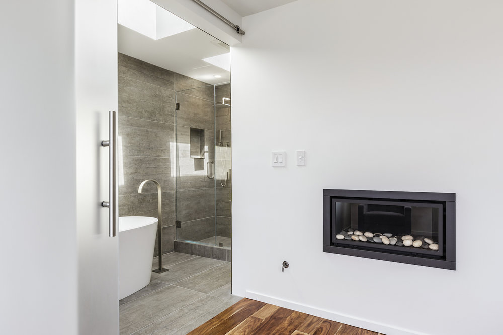 bathroom with fireplace and white tub and brushed nickel fixtures and grey tile and glass doors.jpg