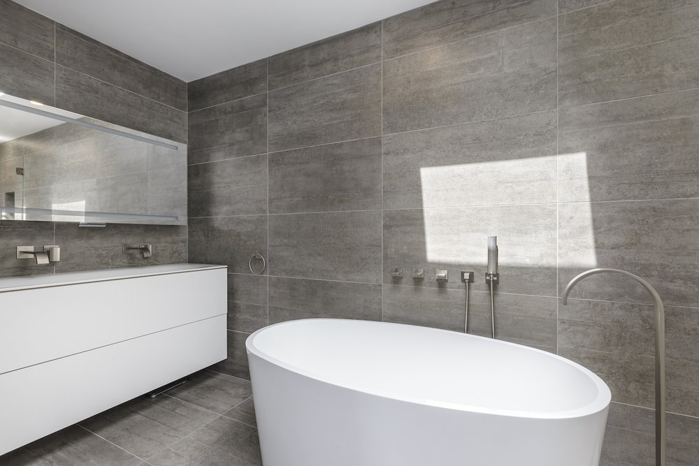 bathroom with grey tile and white vanity and white tub and brushed nickel fixtures.jpg