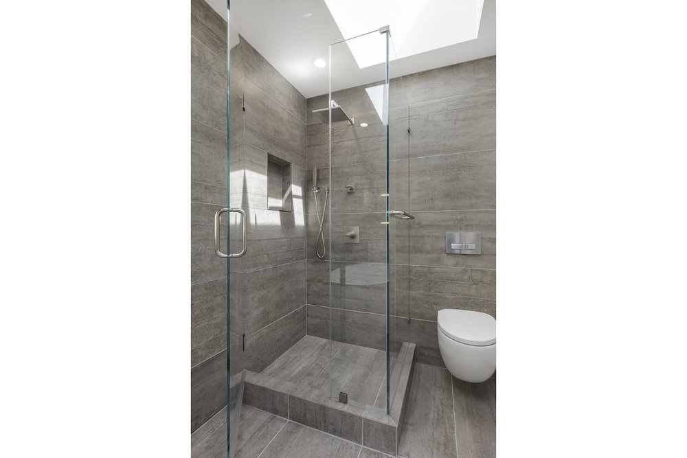 bathroom with stall shower with grey tile and stainless steel fixtures and glass walls.jpg