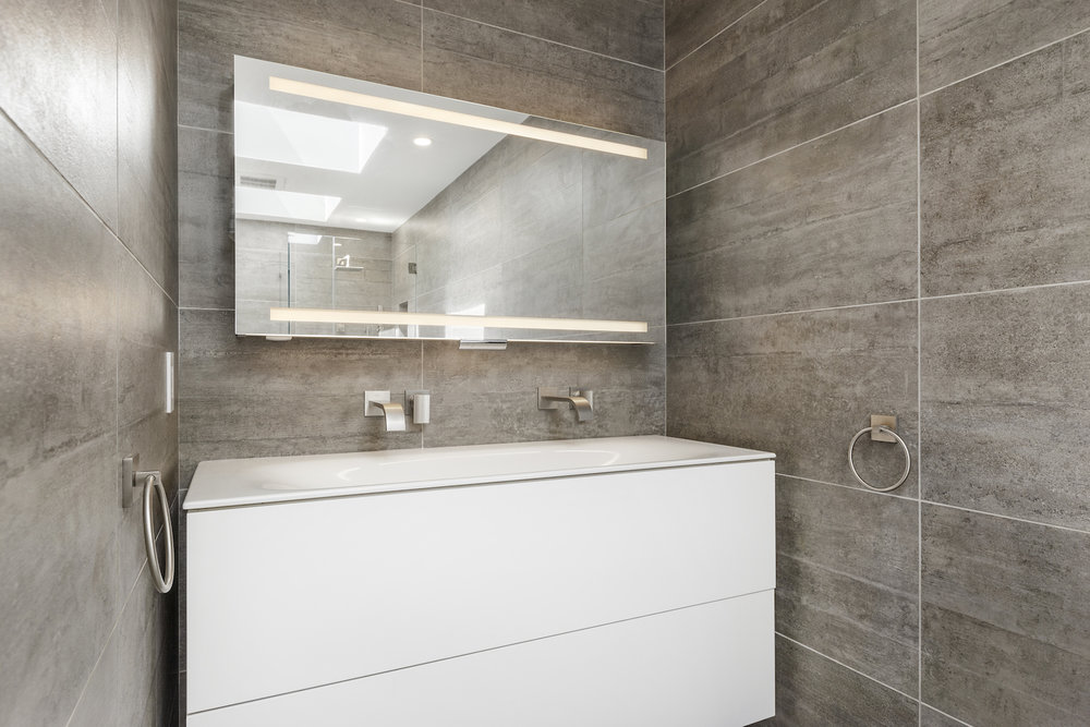 bathroom with grey wall tile and white floating vanity and brushed nickel fixtures.jpg