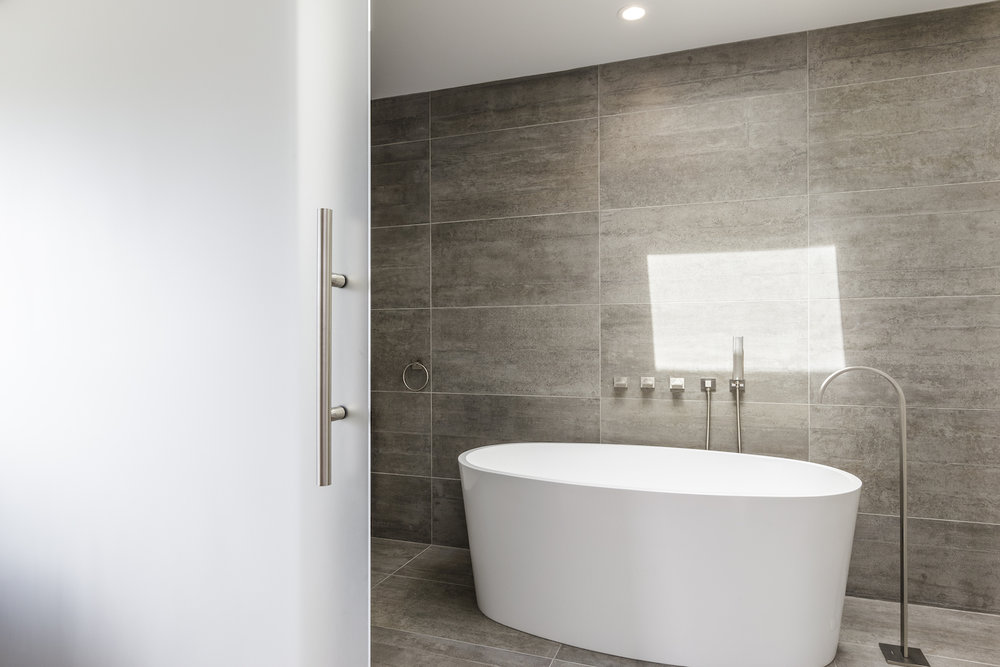 bathroom with white tub and brushed nickel fixtures and glass barn door.jpg