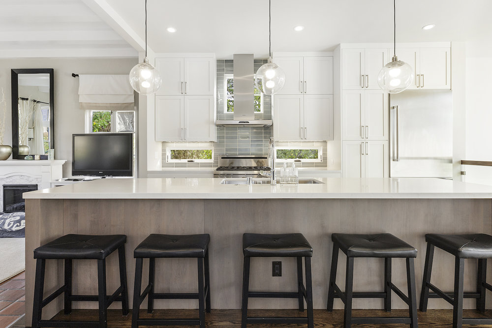 kitchen with large island with seating and white cabinets.jpg