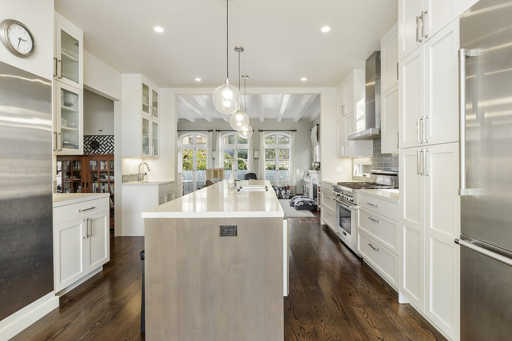 kitchen with white cabinets and stainless steel appliances and large island and wood floors.jpg