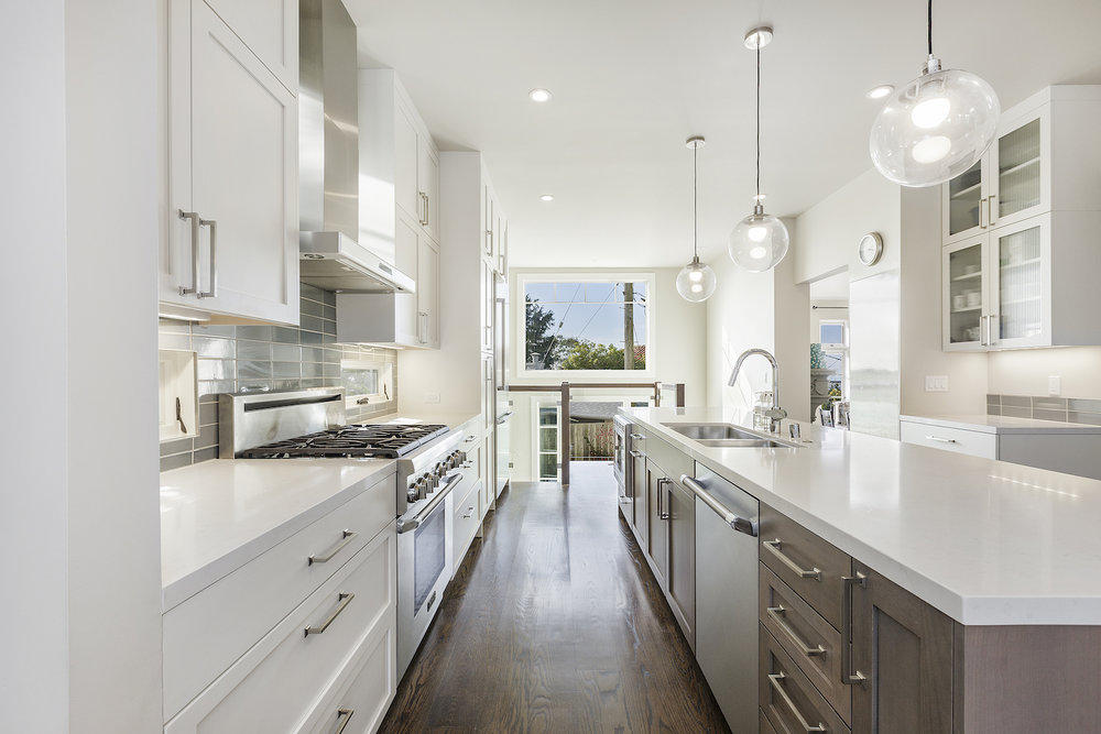 kitchen with white cabinets and wood flooring and stainless steel appliances.jpg
