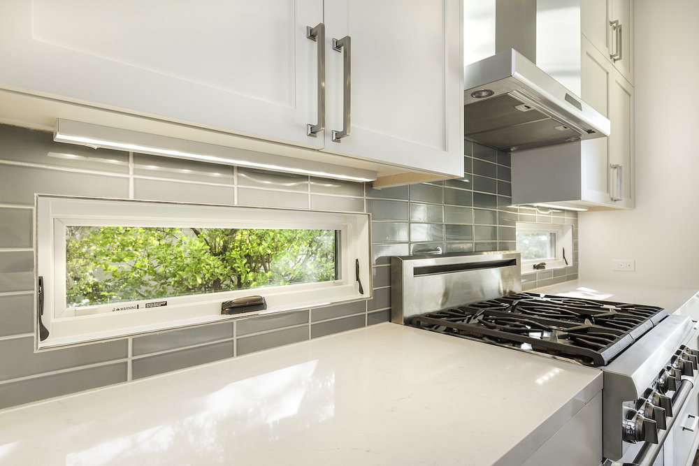 kitchen with white counters and accent windows in grey tile backslash.jpg