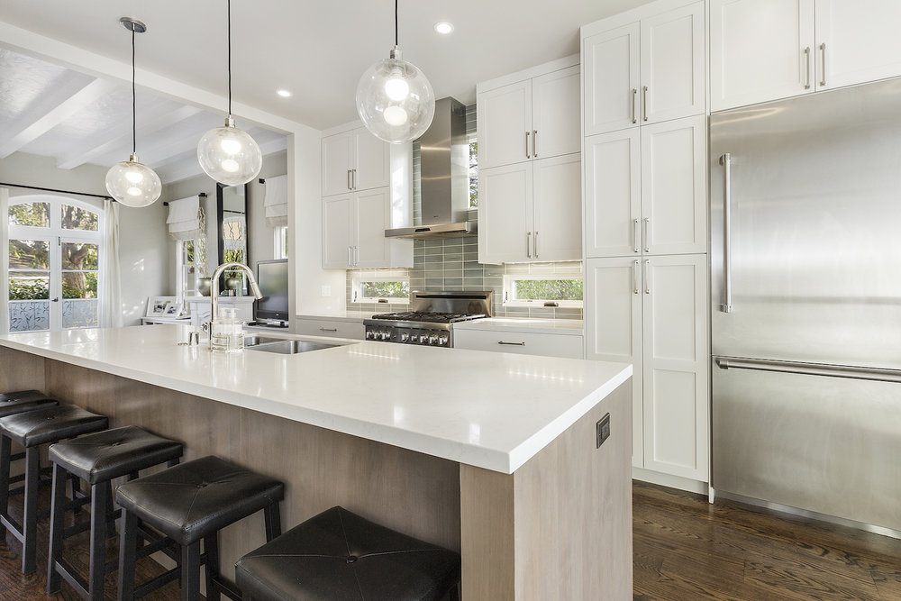 open kitchen with white cabinets and stainless steel appliances and silver cabinet hardware.jpg