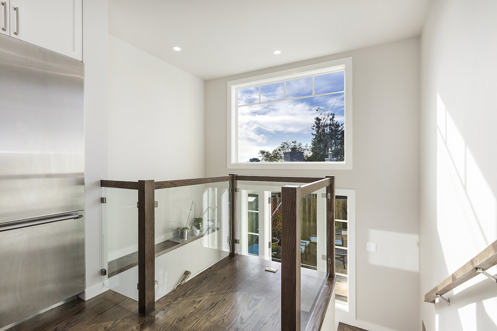 stair landing with wood railing and glass panels and large picture window.jpg