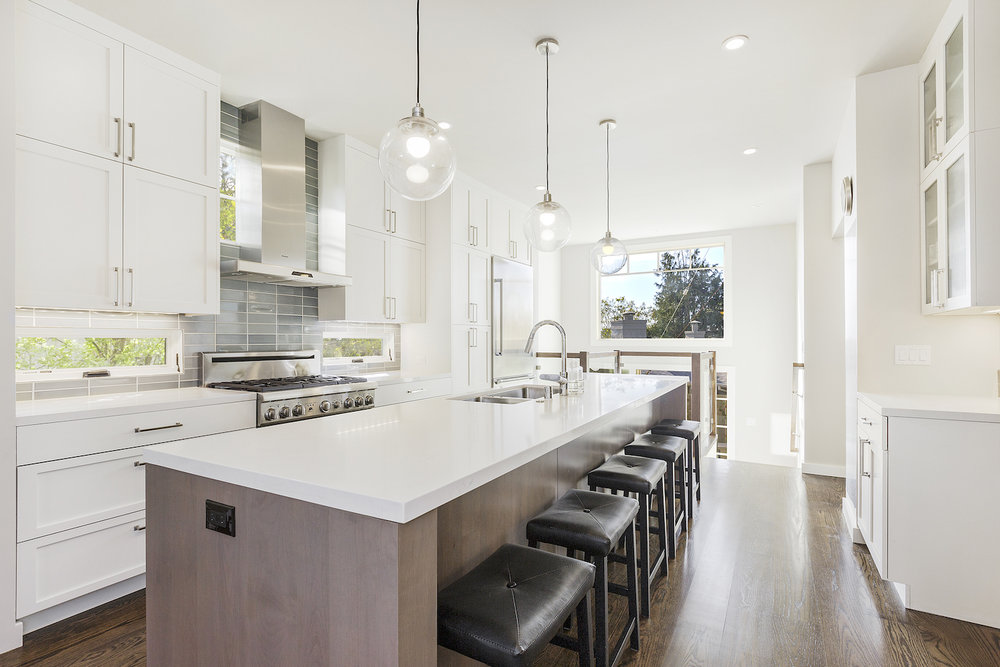 white kitchen with brown wood island and wood flooring and stainless steel appliances.jpg