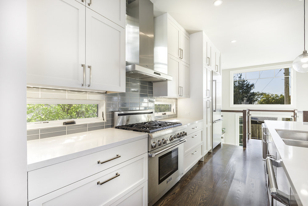 white kitchen with grey tile backsplash and window inserts and wood floors and stainless steel appliances.jpg