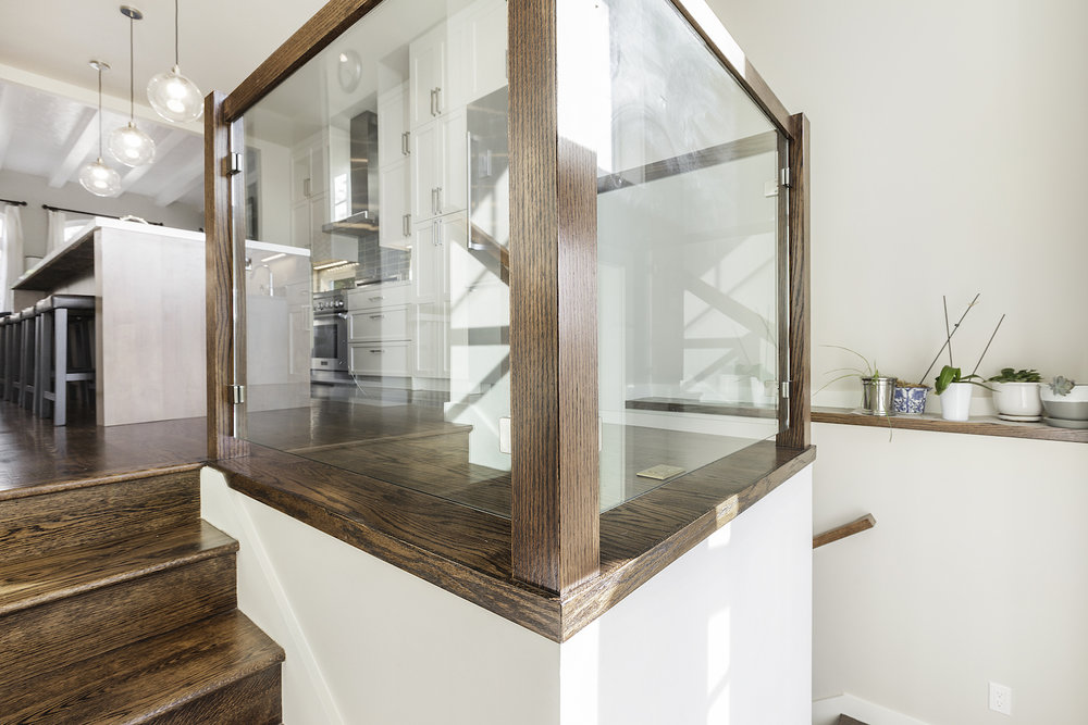 wooden stairs with accent shelving on walls and glass paneled landing area.jpg