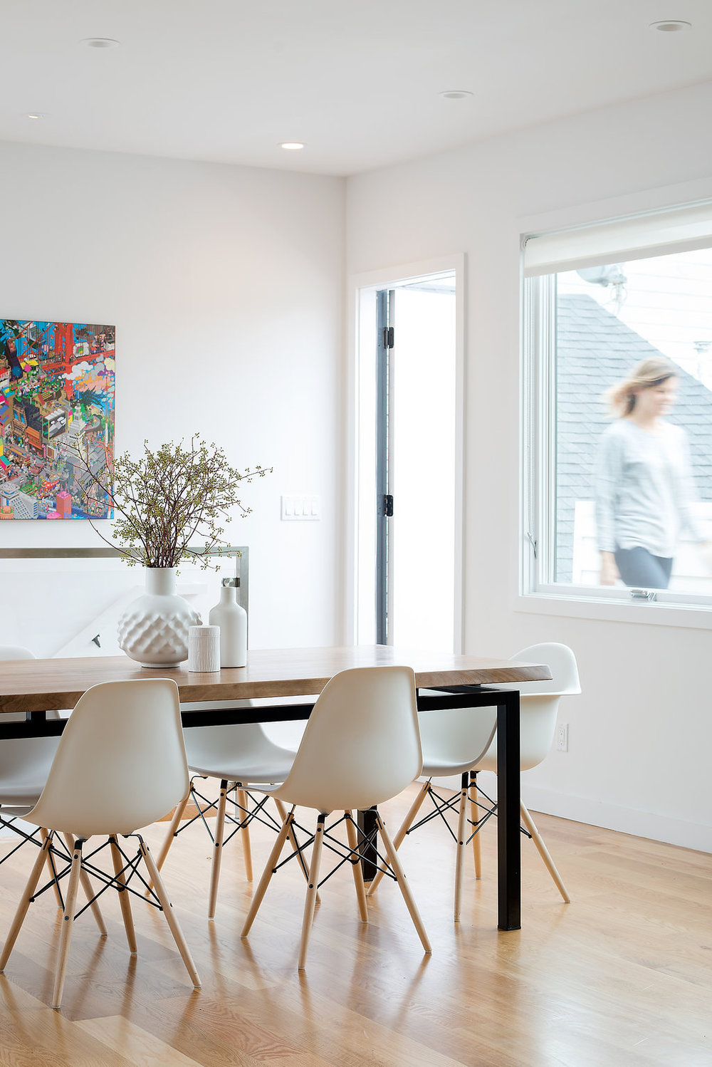 dining area with wood and metal table and white dining chairs and light wood flooring.jpg