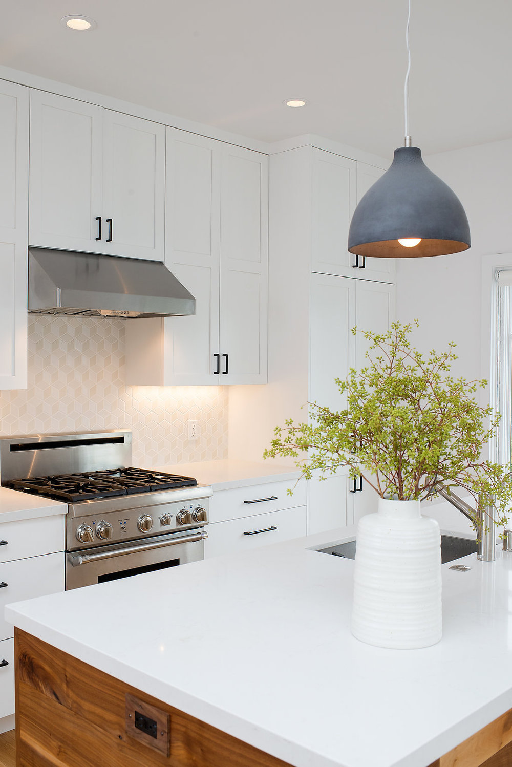 kitchen with white marble counters and white cabinets and stainless steel appliances.jpg