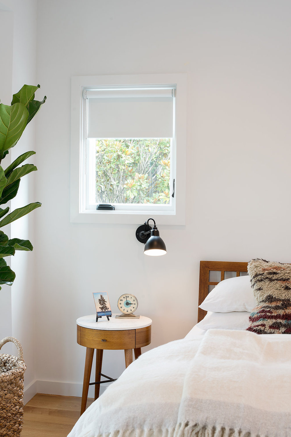 bedroom with wooden bed frame and wood nightstand and white walls and black wall fixture.jpg
