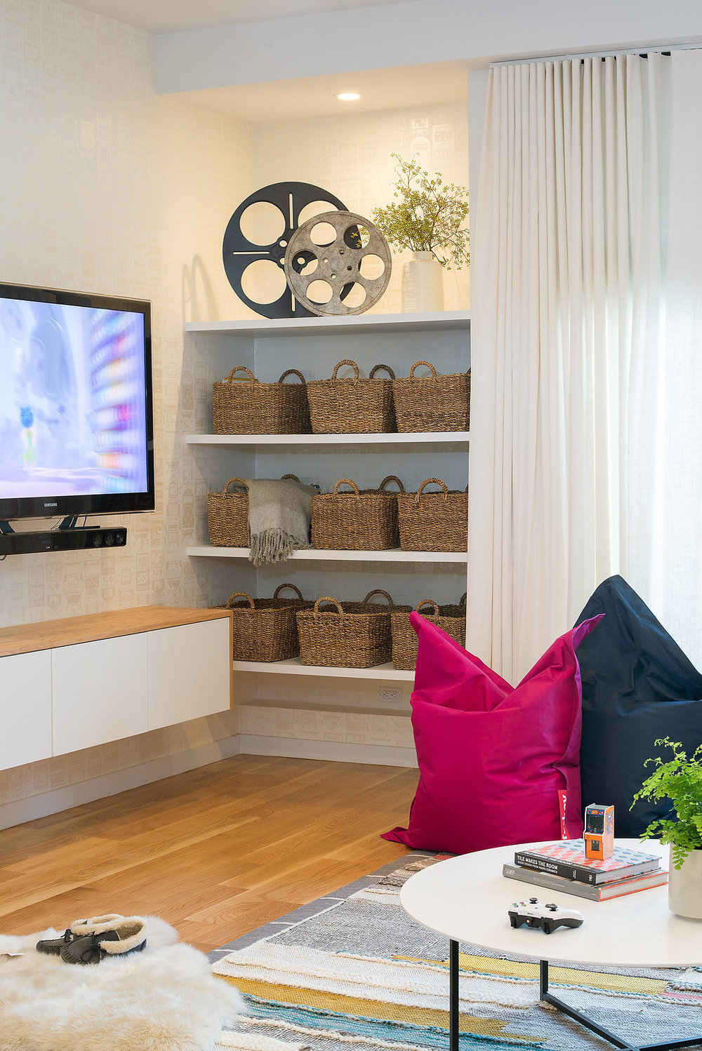 living area with open storage shelving with wicker baskets and wood flooring and colorful floor cushions and floating entertainment storage and white coffee table.jpg