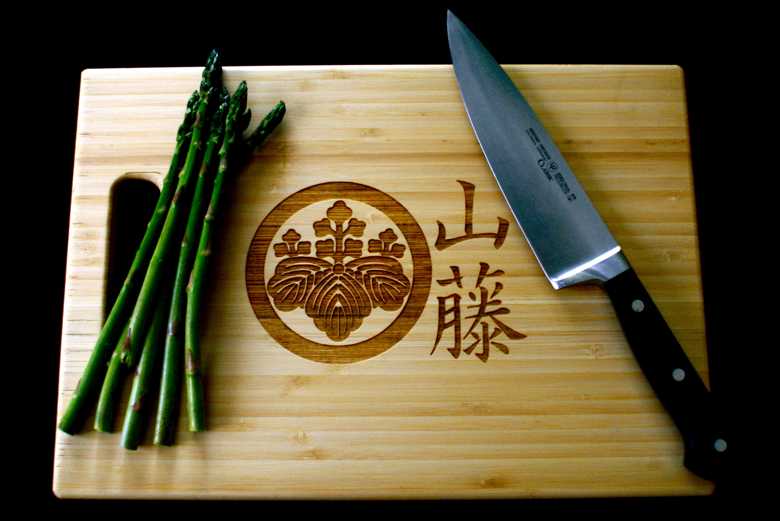 A Family Crest engraved onto a bamboo cutting board.