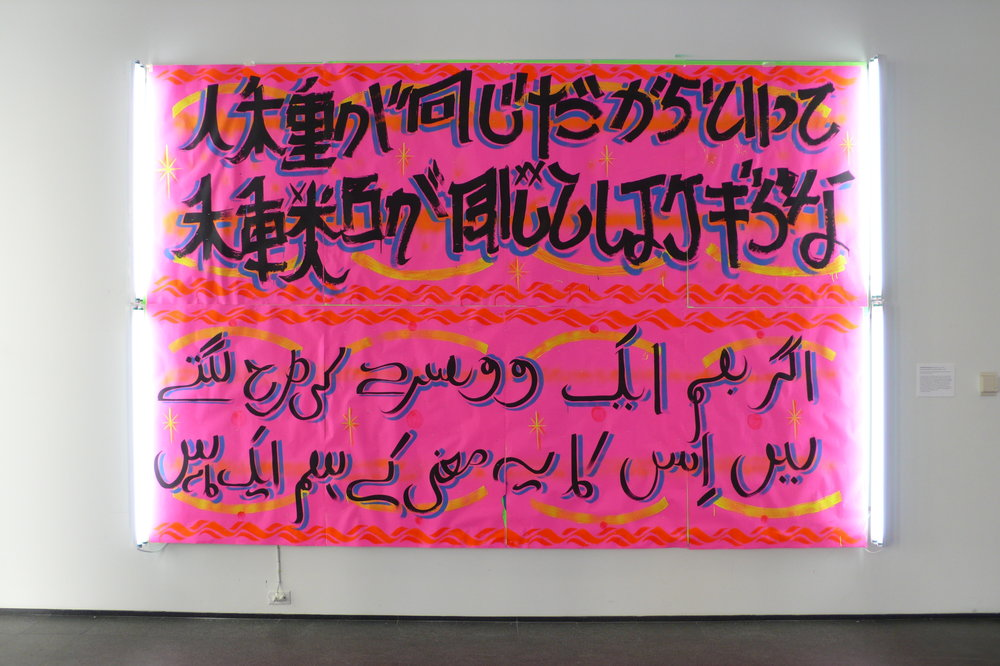 """""""All my skin folk ain't all my kin folk,""""  (Zora Neale Hurston) Sign paint, fluorescent lighting fixtures, acrylic, and paper on medium density overlay. 2008  Translations from the MCA community are incorporated into """"All my skin folk ain't all my kin folk,' (titled after a quote from Zora Neale Hurston) as an ongoing painting pairing languages from a root source, often beginning with an American English dialect. The work begins to take shape as the voices and languages of the public are transformed into stylized signs. The various dialects paired with one another creates subject matter that is common, though expressed differently. The intent is to bridge cultures through written language and examine the tension between them."""