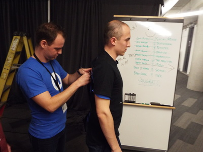 Andris Merkulovs tapes a tearaway T-shirt onto Martins Bratuskins, fellow co-founder of The Monetizr, before the company's pitch on UpTech demo day. On the board behind them are written the names of the pitching companies.