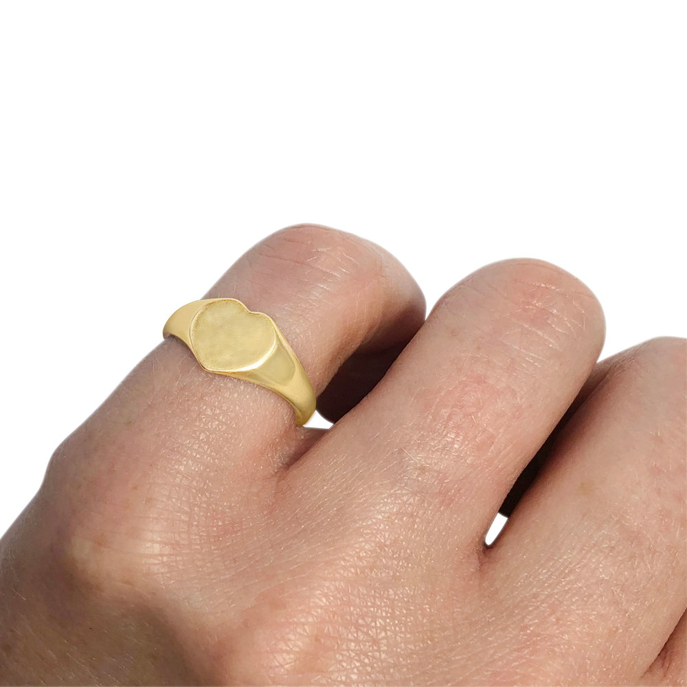 Vintage gold heart-shaped signet ring hand view