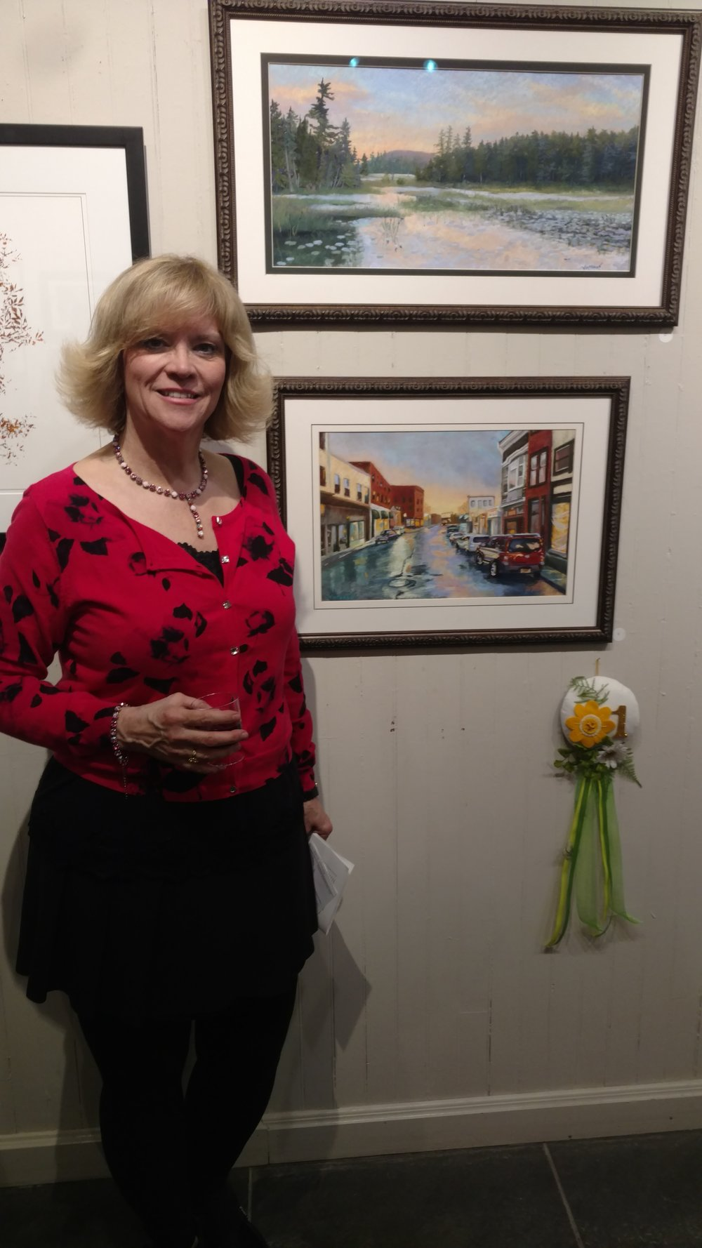 """Susan with her pastel paintings, """"Sunset on Heron Marsh"""" and 1st Place winner, """"Our Little Town."""""""
