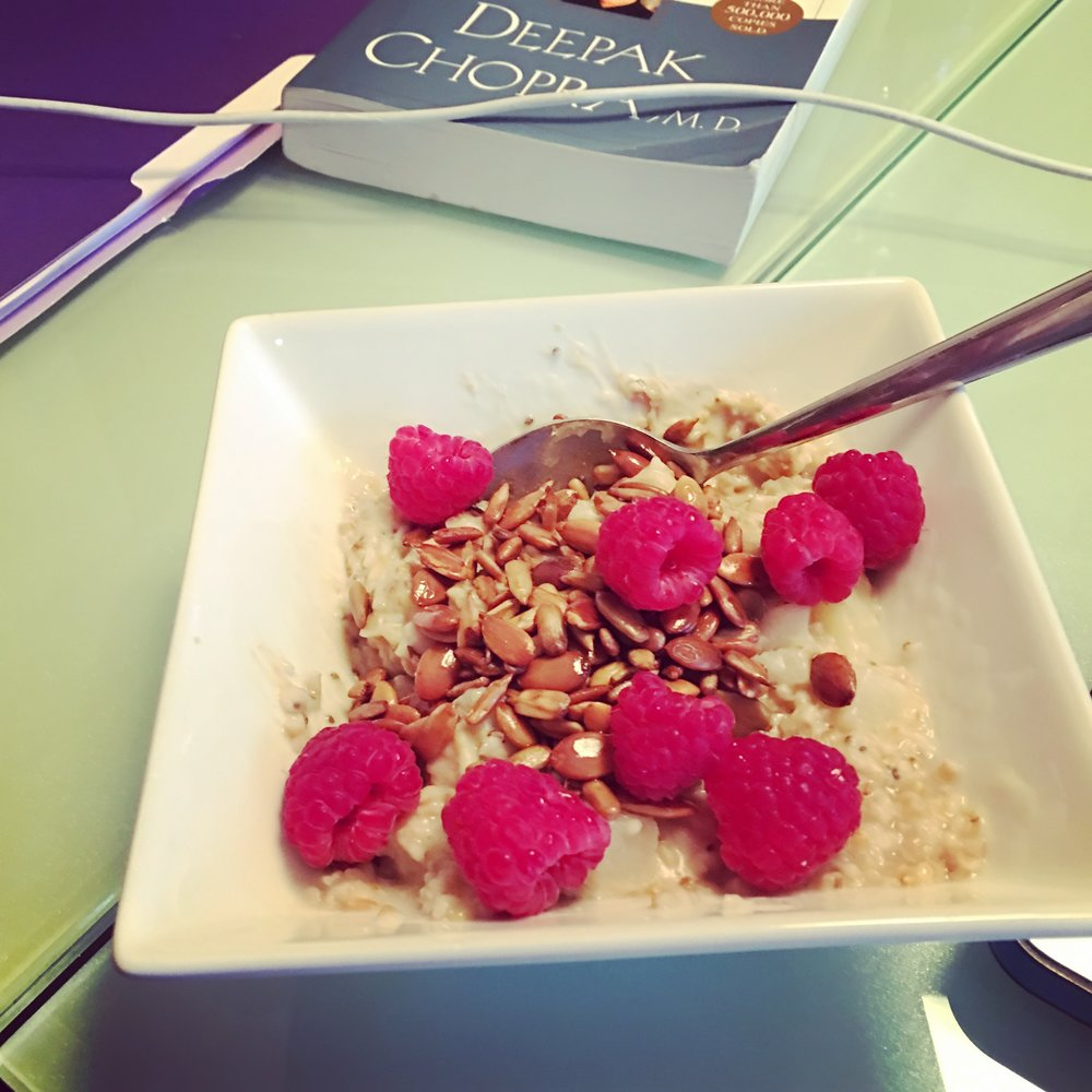 Steel cut oats with pears, toasted sunflower and pumpkin seeds, cashew butter, chia seeds and raspberries. Deepak's book  Perfect Health  in the background.