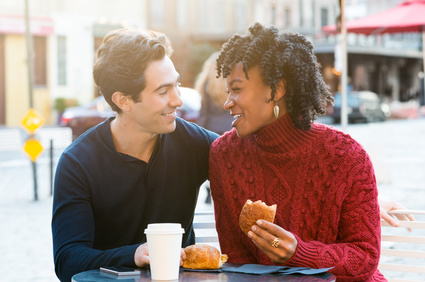 Young romantic couple drinking coffee and eating croissants in a cafe. Young tourist couple enjoying their coffee with breakfast in an outdoor cafe. Smiling couple in a happy conversation while drinking coffee and eating brioches.