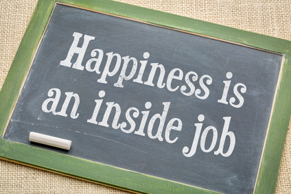 Happiness in an inside job - inspirational words on a vintage slate blackboard with a white chalk against burlap canvas