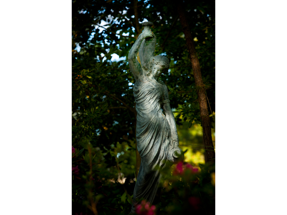 Statue of woman with flowers in the forest photograph