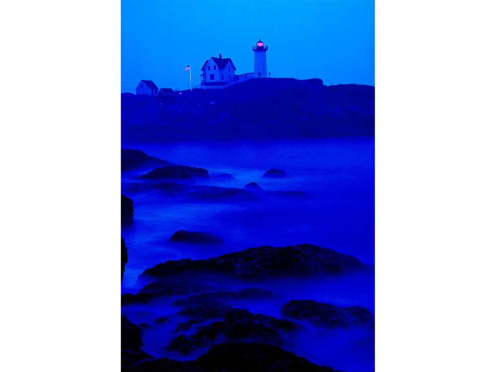 Photograph of a Maine  lighthouse in blue mist and ocean