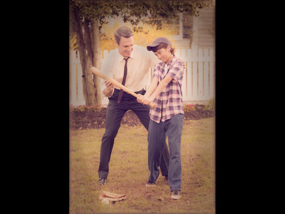 Retro photo of dad teaching son to bat baseball