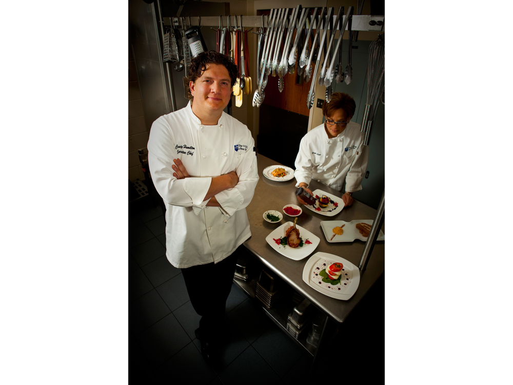Portrait of Chef in restaurant kitchen with sous chef platting food