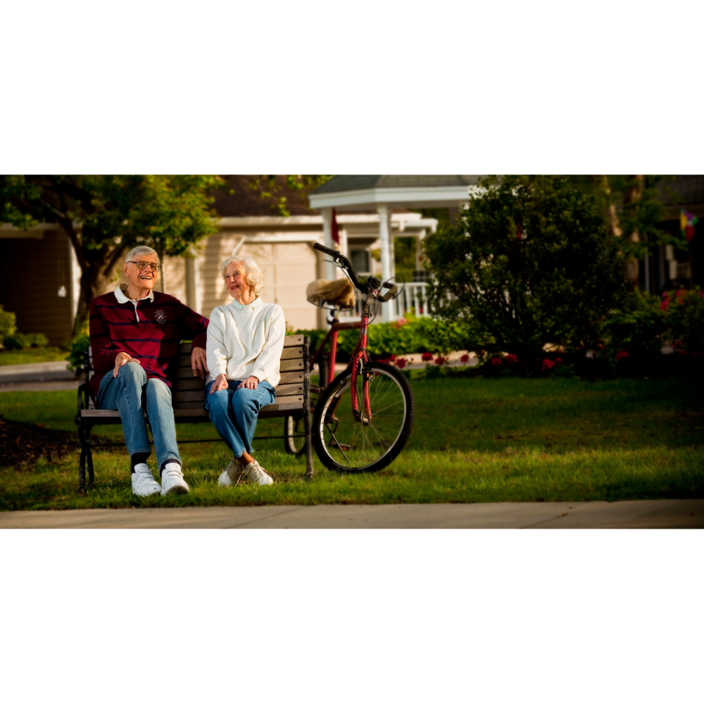 Senior couple on bench with bike by photographer Craig Anderson