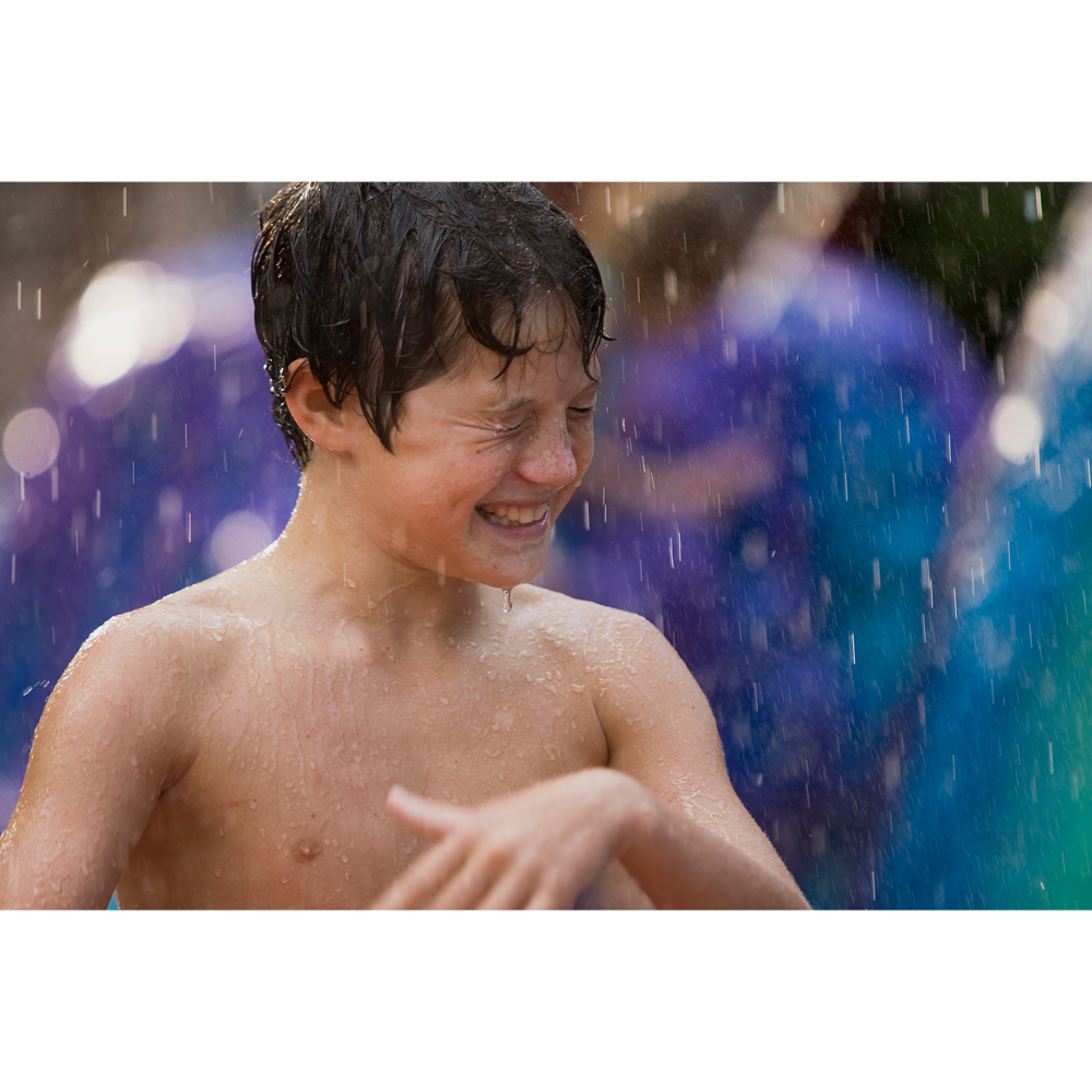 Boy getting rained on at water park