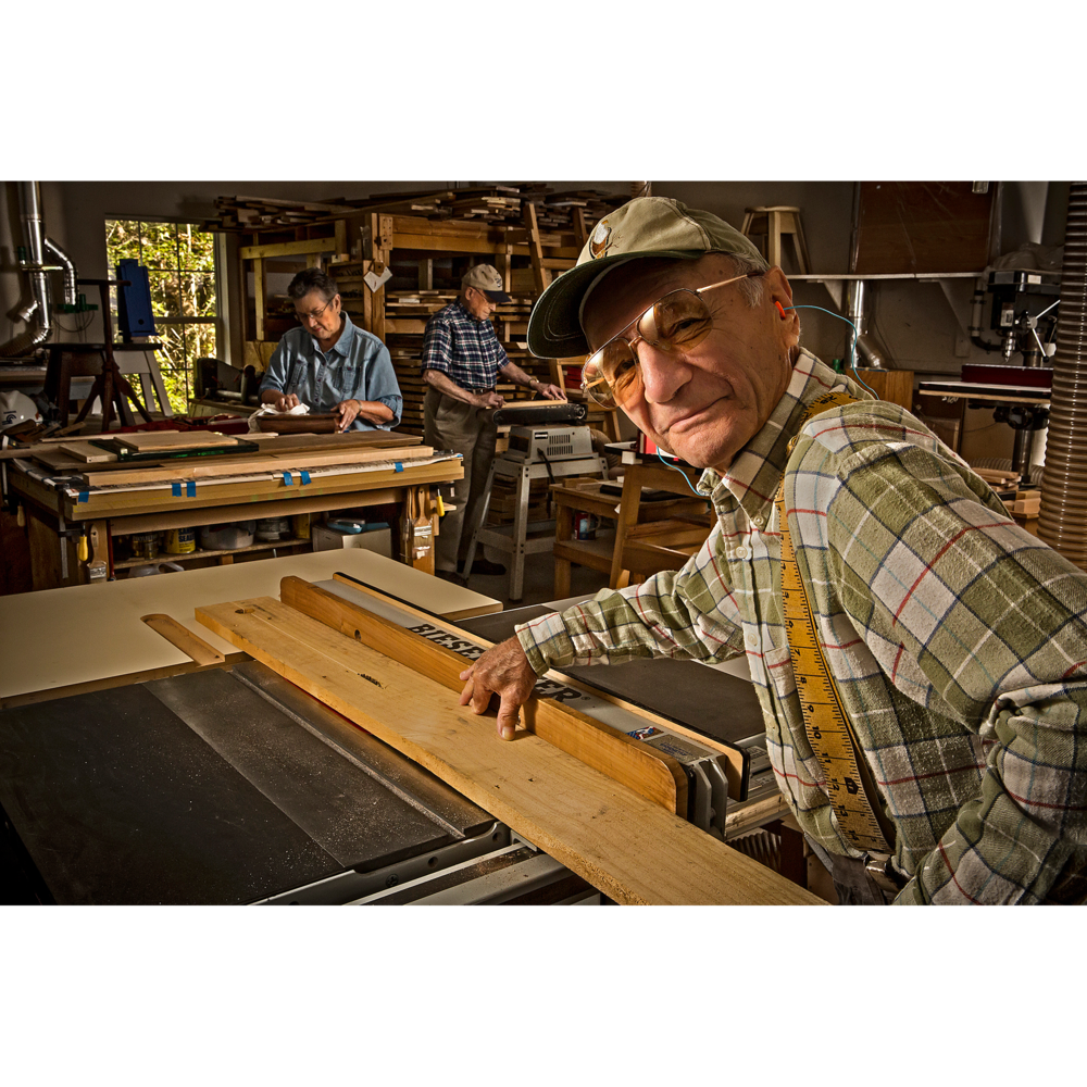 Senior man in woodworking shop sawing wood