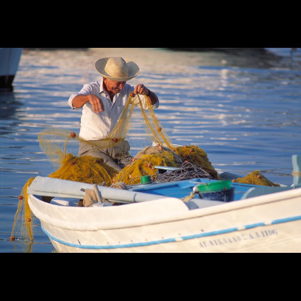 Photograph of a Greek fisherman in fishing boat tending nets