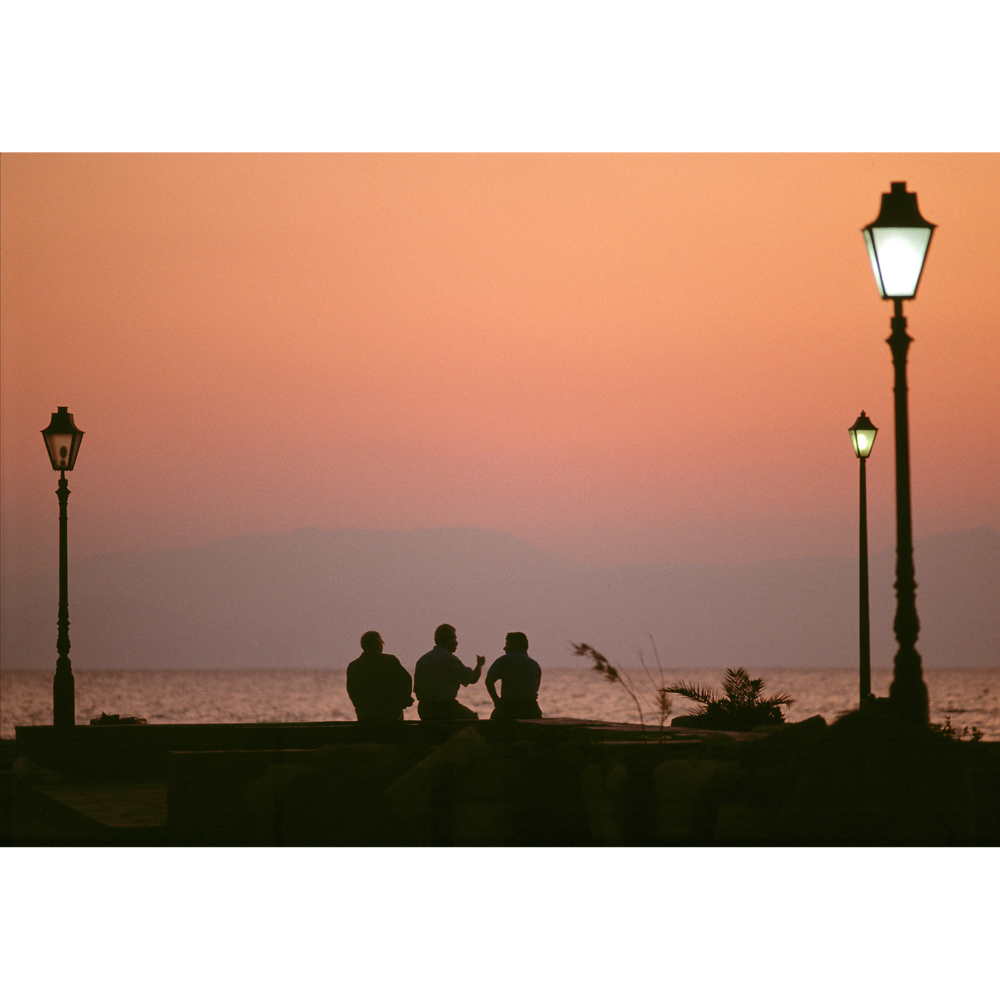Greek men at sunset overlooking water photograph