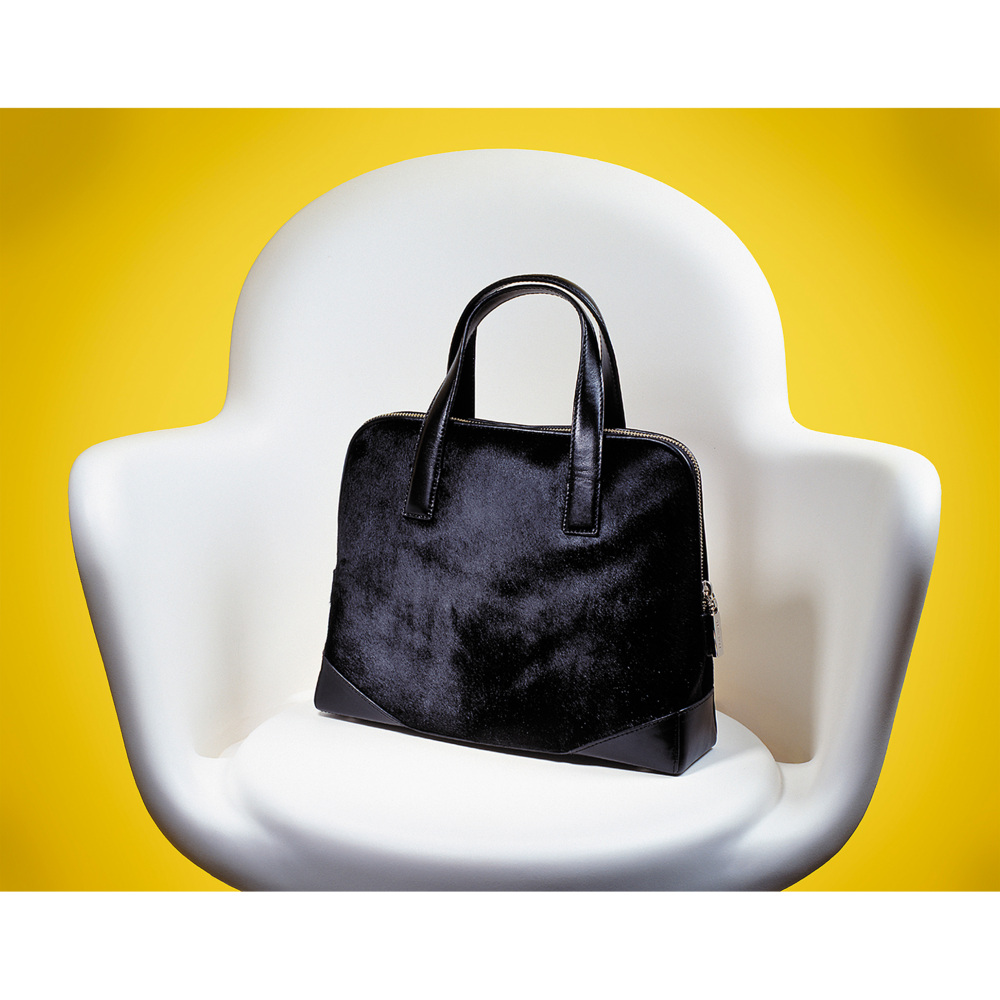 Cowhide purse in white chair by photographer Craig Anderson