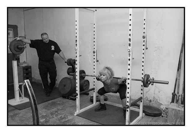 woman being coached in the squat
