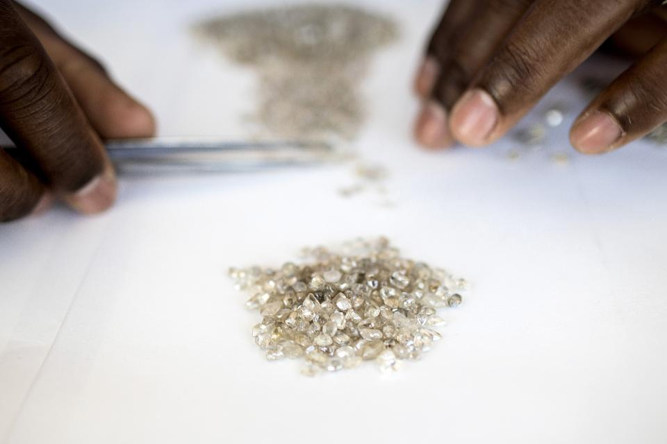 An employee grades a pile of rough diamonds at the Namibian Diamond Trading Co. (NTDC) diamond processing and valuation center. The world's biggest diamond producer has spent $157 million on a state-of-the-art exploration vessel that will scour 6,000 square kilometers (2,300 square miles) of ocean floor for gems, an area about 65 percent bigger than Long Island. Photographer: Simon Dawson/Bloomberg