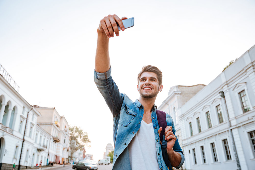 graphicstock-smiling-tourist-with-backpack-making-selfies-isolated-on-beautiful-modern-buildings-located-in-the-city-centre_Sug-kpqB3e.jpg