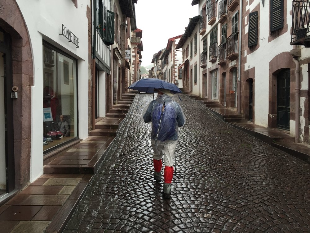 As much as I like this photo of our Camino Provisions teammate walking out of SJPP, the umbrella did not perform well in the wind, but the rest of the gear worked very well on that rainy, rainy day. Note his red rain gaiters, some of our new favorite Camino gear items.