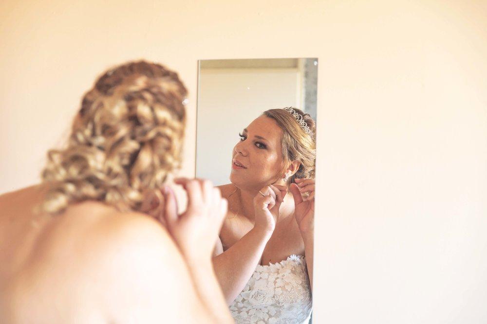Sieraden omdoen door de bruid. Trouw sieraden. oorbellen trouwjurk