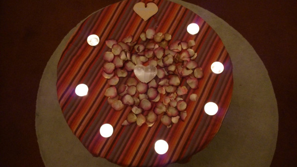 A small personal altar honouring love and loss. The composition comprises tealights, pink rose petals and fragile hearts.