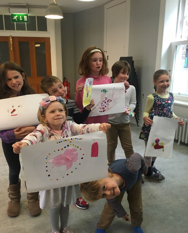 Photo by Rachael King, showing the children displaying their artwork based on the story of The Grumpy Gecko, where a gecko learns that the natural world is a series of connections.
