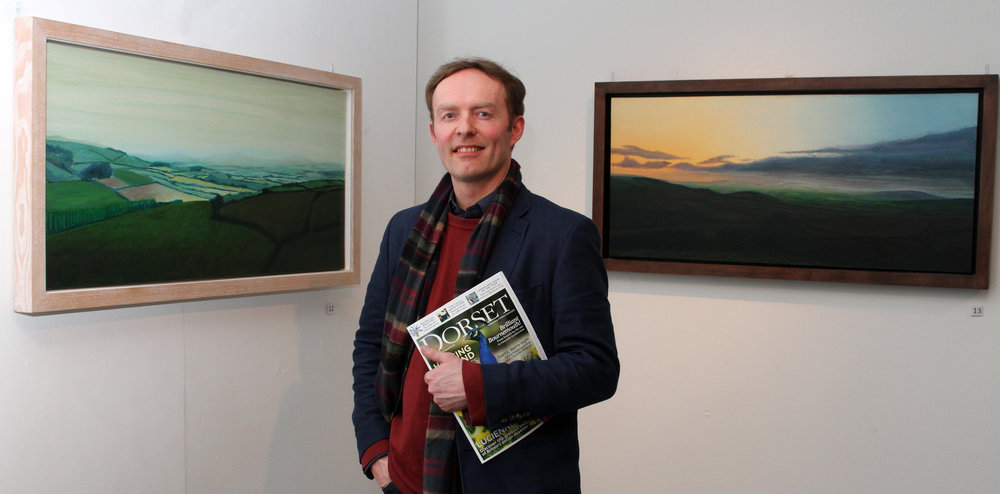 "Kit Glaisyer in front of ""Mists across the Marshwood Vale"" and ""Sunset above the Marshwood Vale"" at the Lighthouse, Poole"